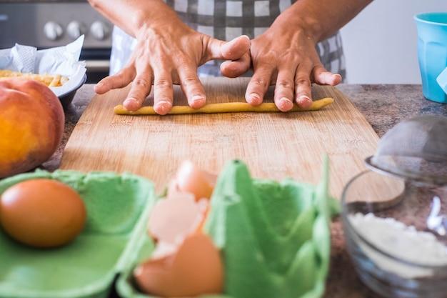 Frauenhand zu hause, die auf alte weise eine pizza oder einen kuchen zubereitet, wie es die großmutter tut - handmande und hausgemachter kuchen und koch- und küchenkonzept für frauen