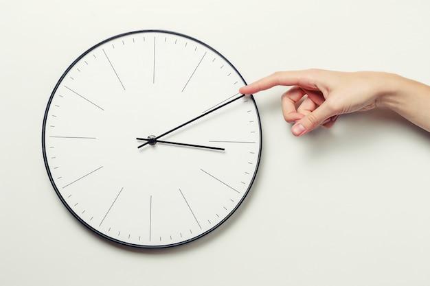 Frauenhandendzeit auf einer runden uhr, einem zeitmanagement und einem fristenkonzept