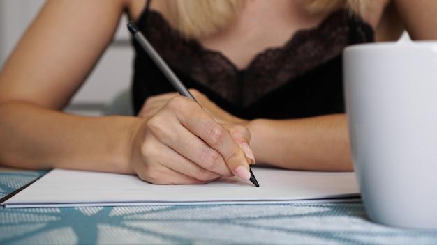 Frauenhandgebrauch bleistiftschreiben auf klarem weißem blatt. weiße tasse. fernarbeit oder studium