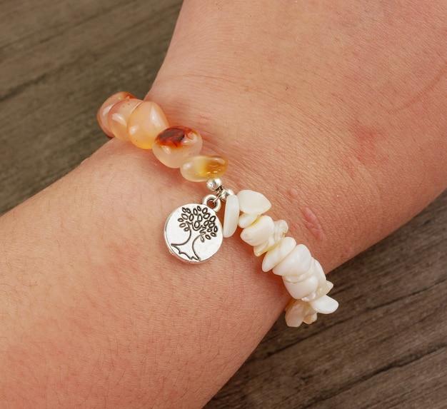 Frauenhandgelenk, das perlenbesetztes armband auf hölzernem hintergrund trägt