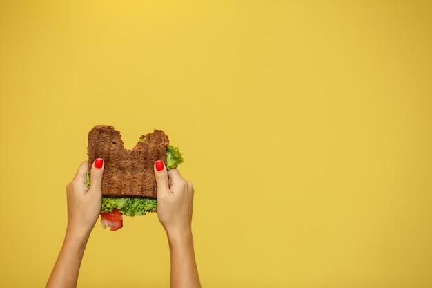 Frauenhandgriff gebissenes sandwich auf gelbem hintergrund. sandwich-promotion-konzept
