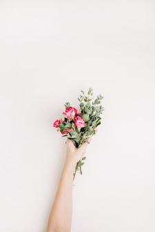 Frauenhandgriff rosafarbene blumen und eukalyptusblumenstrauß auf weißem hintergrund. flache lage, ansicht von oben