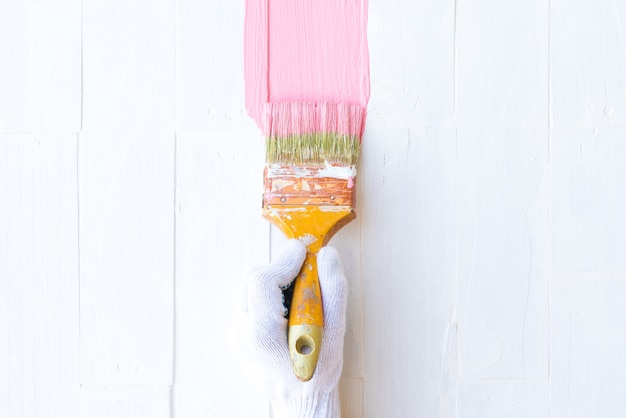 Frauenhandholdingbürste, die rosa farbe auf einem weißen holztisch malt