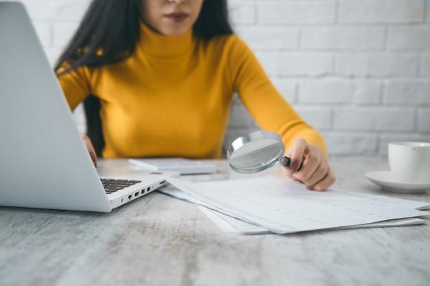 Frauenhandlupe und dokument auf dem schreibtisch