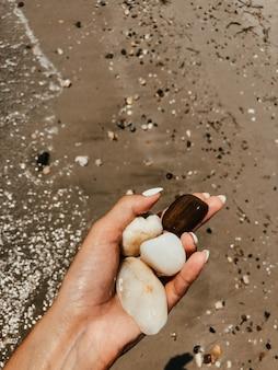 Frauenhandmaniküre, die weiße schöne steine über dem sandigen sommerstrand des meeres hält. natürlicher hintergrund