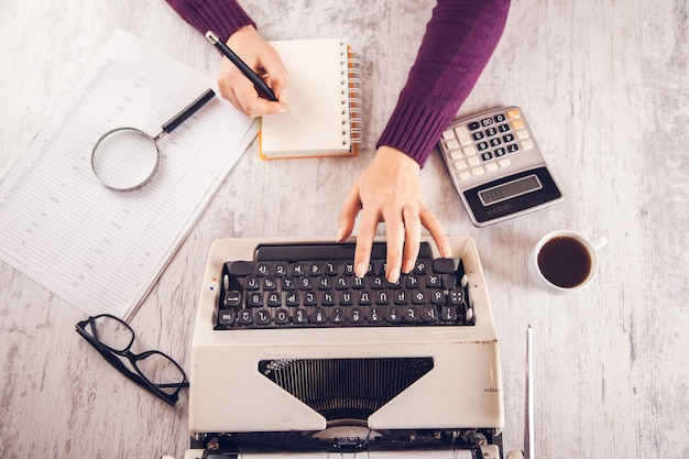 Frauenhandnotizblock und schreibmaschine auf tisch