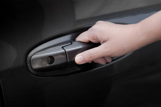 Frauenhandoffene autotür, hand, die den türgriff eines autos zieht