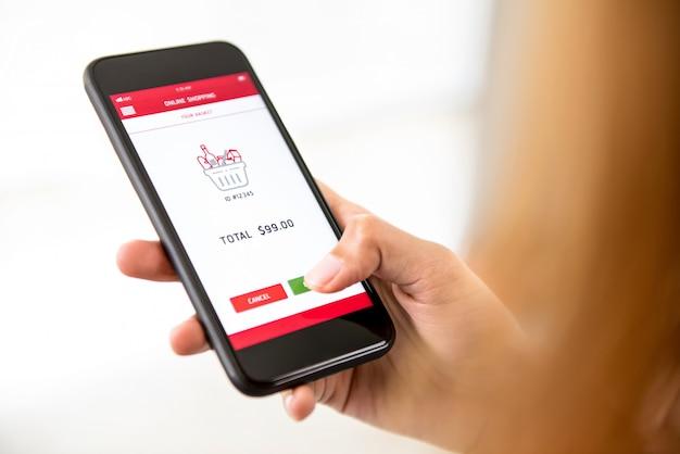 Frauenhandrührender smartphoneschirm, lebensmittelgeschäfte online kaufend
