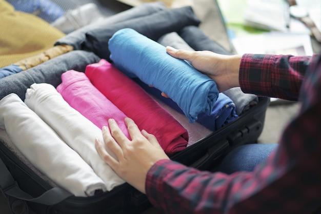 Frauenhandsatzkleidung in der koffertasche auf bett, bereiten sich für neue reise vor.