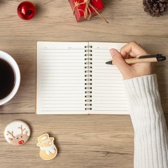 Frauenhandschrift auf notebook mit schwarzer kaffeetasse und weihnachtsplätzchen auf dem tisch. weihnachten, frohes neues jahr, ziele, auflösung, aufgabenliste, strategie und plankonzept