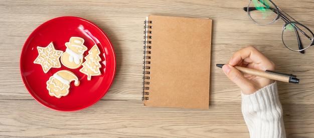 Frauenhandschrift auf notebook mit weihnachtsplätzchen auf dem tisch. weihnachten, frohes neues jahr, ziele, auflösung, aufgabenliste, strategie und plankonzept