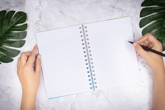 Frauenhandschrift in einem leeren notizbuch der weißen seite auf weißem marmorschreibtisch