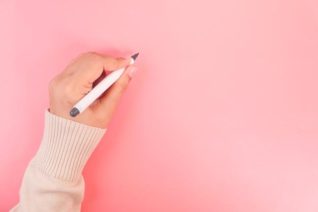 Frauenhandschrift mit stift auf rosa hintergrund.