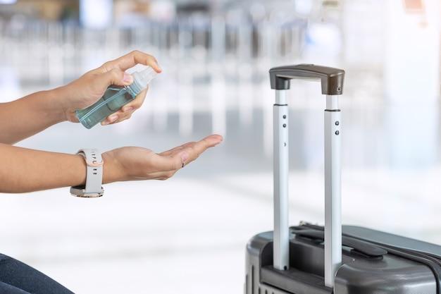 Frauenhandsprühalkohol-desinfektionsmittel nach halten des griffs gepäcktasche im flughafenterminal