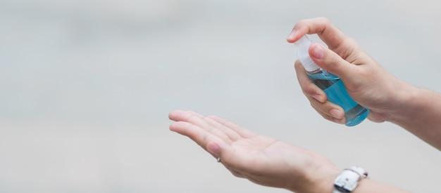 Frauenhandsprühhand-alkohol-desinfektionsflaschenspender gegen neuartiges coronavirus oder corona-virus-krankheit (covid-19) im öffentlichen freien.