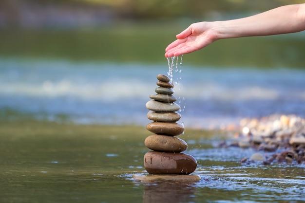 Frauenhandströmendes wasser auf den steinen balanciert wie pyramide