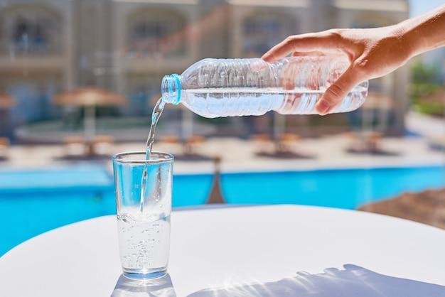 Frauenhandströmendes wasser in einem glas von der plastikflasche agains swimmingpoolhintergrund