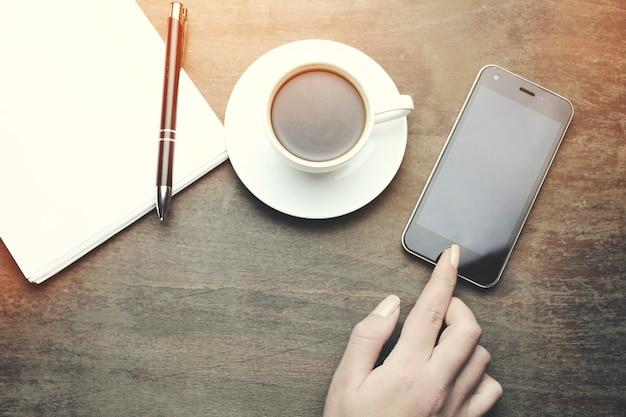 Frauenhandtelefon, auf holztischnotizbuch, stift und tasse kaffee