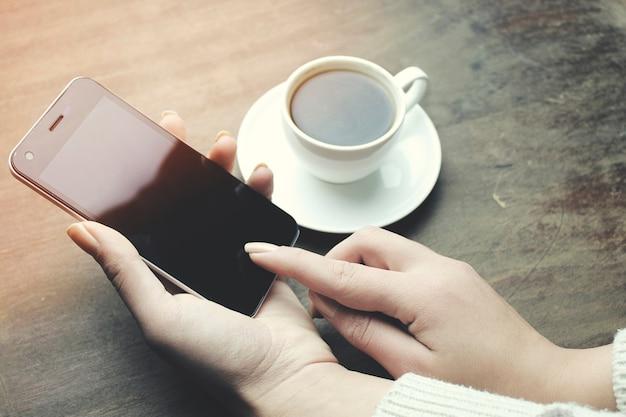 Frauenhandtelefon und kaffee auf holztisch