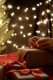 Frauenhandverpackungsweihnachtsgeschenkbox mit bokeh-lichterhintergrund