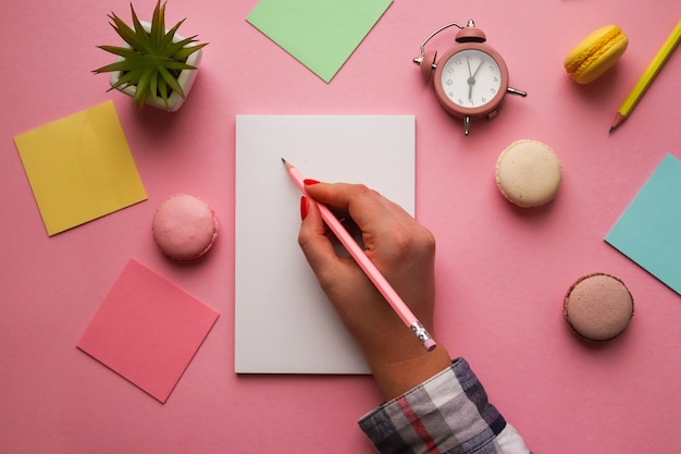 Frauenhandzeichnung im album. arbeitsplatz mit skizzenbuch, stiften, wecker, pflanze, makronen