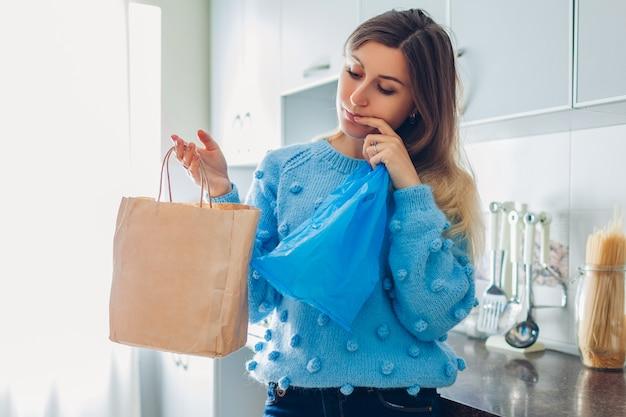 Frauenhausfrau, die zwischen öko- und polyethylenpaket auf küche zu hause wählt