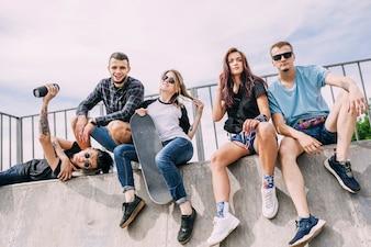 Frauenholding-Skateboard, das mit Freunden auf Rampe sitzt