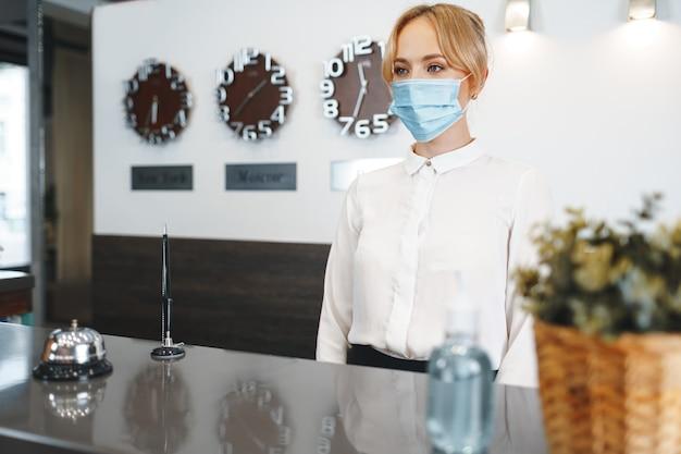 Frauenhotelrezeptionistin, die medizinische maske trägt, um vor coronavirus zu schützen