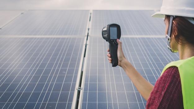 Fraueningenieur, der wärmebildkamera verwendet, um temperaturhitze des sonnenkollektors zu überprüfen