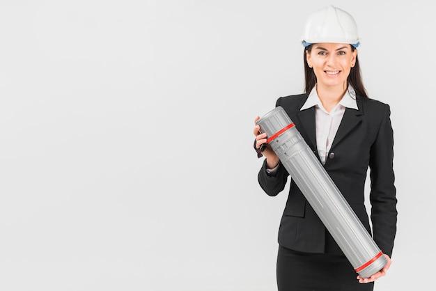 Fraueningenieur im sturzhelm, der rohr hält