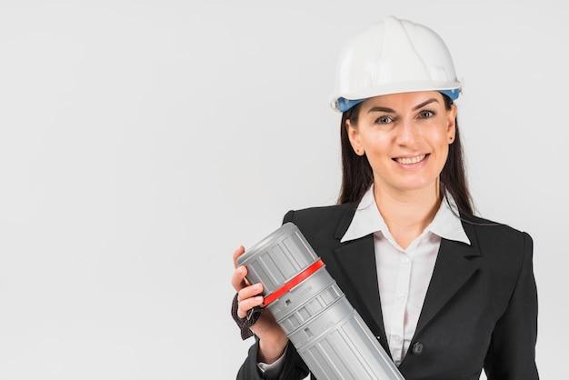 Fraueningenieur im weißen sturzhelm, der rohr hält