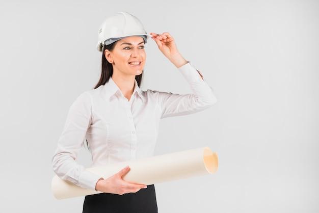 Fraueningenieur im weißen sturzhelm mit whatman-papier
