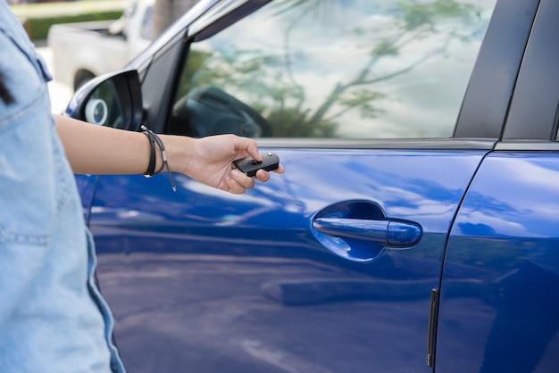 Frauenjugendliche hand drückt auf das blaue auto der fernbedienung im parkplatz im freien