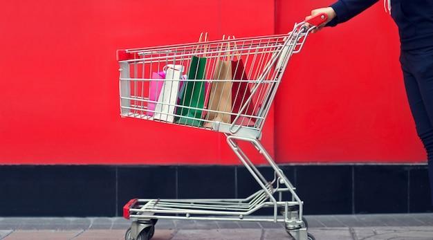 Frauenkäufer und -einkaufstasche in einer laufkatze oder im einkaufswagen auf roter wand das mall backgrou