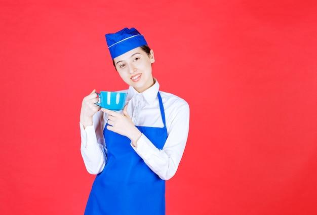Frauenkellnerin in uniform, die eine blaue tasse auf roter wand steht und hält.