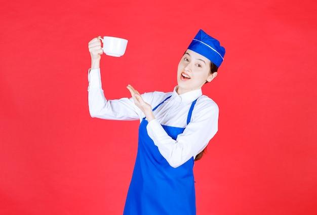 Frauenkellnerin in uniform, die eine tasse an der roten wand steht und hält.