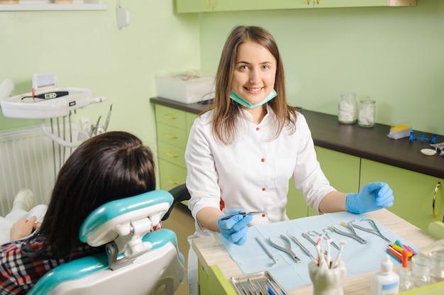Frauenkieferorthopäde, der zahnmedizinisches gerät für das reparieren von zähnen hält