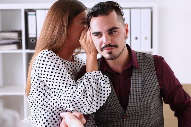 Frauenklatsch flüstert einem mann ins ohr der nachrichten