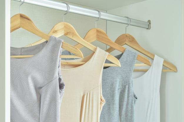 Frauenkleider auf kleiderbügeln im schrank