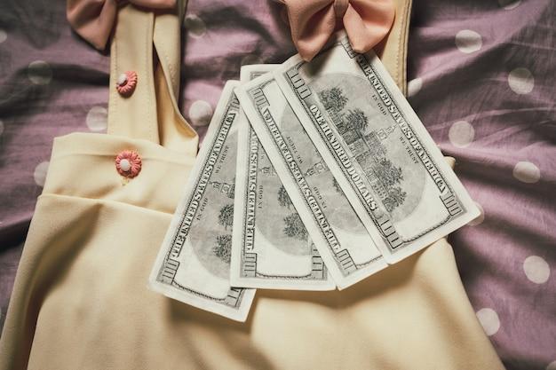 Frauenkleider, die mit dollarbanknoten gepaart wurden.