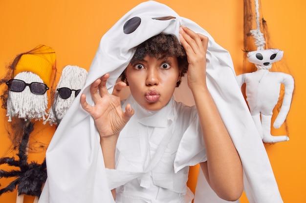 Frauenkleider im mumienkostüm versucht zu erschrecken bereitet sich auf die halloween-feier vor, steht auf orange mit hängenden gruseligen spielzeugen dahinter