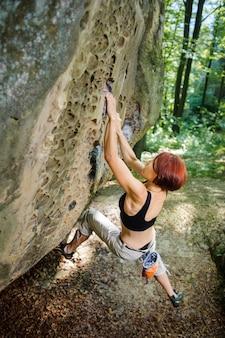 Frauenkletterer, der am großen flussstein hängt. draussen