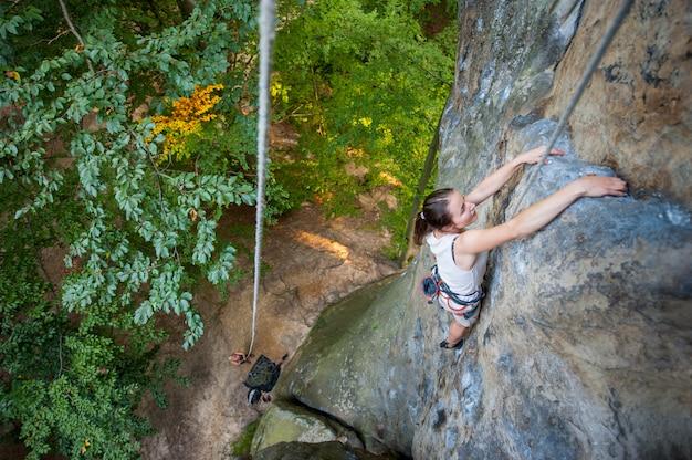 Frauenkletterer klettert auf einer felsigen wand