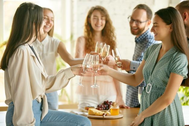 Frauenklirrende gläser mit wein oder champagner.