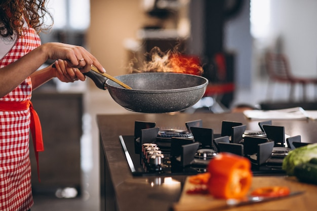 Frauenkoch, der gemüse in der pfanne kocht