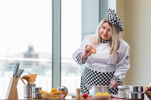 Frauenkoch, der in der hellen küche arbeitet