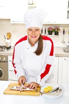 Frauenkoch, der makrelenfilet vorbereitet