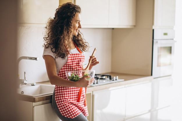 Frauenkoch, der salat an der küche macht