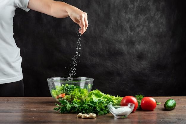 Frauenkoch salzt das gemüse und bereitet salat auf holz zu.
