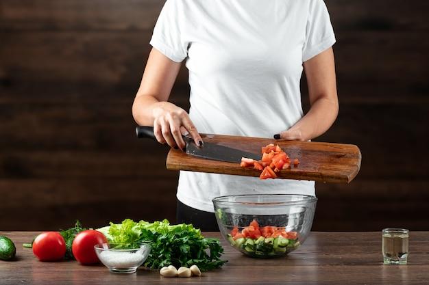 Frauenkoch schneidet gemüse für salatvorbereitung auf holz.